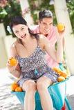 Homme poussant le femme dans la brouette Image stock
