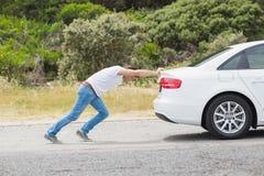 Homme poussant son véhicule Photographie stock libre de droits