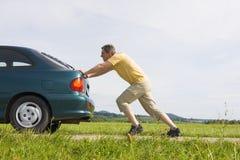 Homme poussant son véhicule Images stock