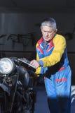 Homme poussant une motocyclette Photographie stock