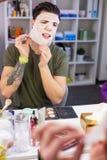 Homme précis dans le T-shirt vert enlevant le masque blanc photo stock