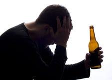 Homme préoccupé avec une bouteille de bière Photos libres de droits