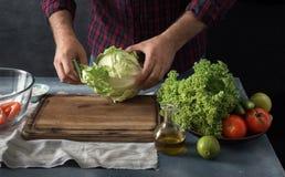 Homme préparant la salade de légumes dans la cuisine à la maison Image stock