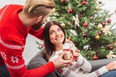Homme présent le cadeau de Noël à l'amie Photographie stock libre de droits