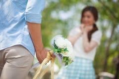Homme prêt à donner des fleurs à l'amie Image stock