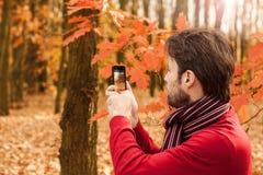 Homme prenant à automne la photo extérieure avec le téléphone portable Image stock