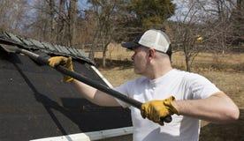 Homme prenant des bardeaux outre d'un toit de hangar Image libre de droits