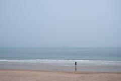 Homme prenant des photos de mer loin sur la plage Photographie stock