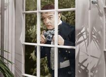 Homme prenant des photos par la fenêtre images stock