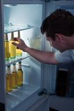 Homme prenant la bière d'un réfrigérateur Photos libres de droits
