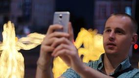 Homme prenant la photo avec le téléphone d'appareil-photo la nuit Jeune homme occasionnel prenant la photo avec le téléphone d'ap clips vidéos