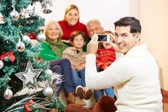 Homme prenant la photo de famille à Noël Images stock