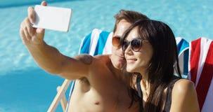 Homme prenant la photo de se avec l'épouse à la piscine Images stock