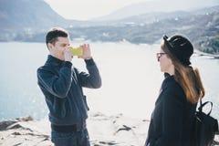 Homme prenant la photo de son amie à l'aide de son smartphone près du bord de la mer et des montagnes Photos libres de droits