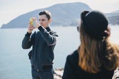 Homme prenant la photo de son amie à l'aide de son smartphone près du bord de la mer et des montagnes Photographie stock