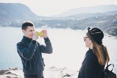 Homme prenant la photo de son amie à l'aide de son smartphone près du bord de la mer et des montagnes Image stock