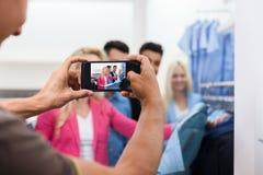 Homme prenant la photo des jeunes faisant des emplettes, amies de sourire heureuses deux clients de couples dans la boutique de m Photo stock