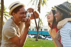 Homme prenant la photographie des femmes en parc Images stock
