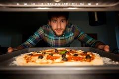 Homme prenant la pizza du four Photo libre de droits