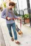 Homme prenant le chien pour la promenade sur la rue de ville photographie stock