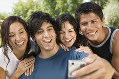 Homme prenant un autoportrait avec ses amis Photos stock