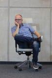 Homme presque chauve de Moyen Âge avec la mauvaise position assise de lunettes sur la chaise dans le bureau Image stock