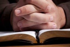Homme priant avec la bible Photographie stock