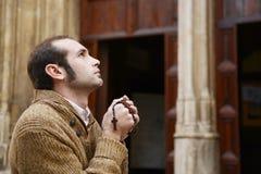 Homme priant dans l'église retenant des petits programmes de prière Photos libres de droits