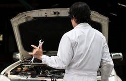 Homme professionnel de mécanicien tenant la clé et sa main avec je t'aime le signe avec la voiture dans le capot ouvert au garage Images libres de droits