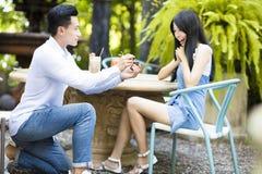 Homme proposant à la bague de fiançailles de offre d'amie Photos stock