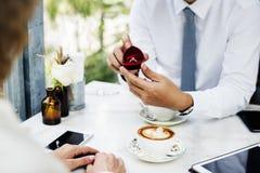 Homme proposant l'amie avec la bague à diamant au café Photographie stock libre de droits