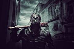 Homme psychopathe dans le masque d'hockey avec la batte de baseball ensanglantée Images stock