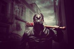 Homme psychopathe dans le masque d'hockey avec la batte de baseball ensanglantée image stock