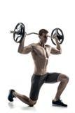 Homme puissant se tenant sur le genou et tenant le barbell image stock
