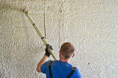 Homme pulvérisant le stuc concret pour murer Images libres de droits