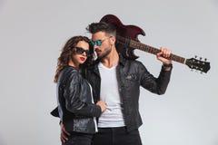Homme punk frais tenant la guitare sur l'épaule et embrassant la femme Image libre de droits