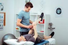 Homme qualifi? bel faisant un massage de jambe image libre de droits
