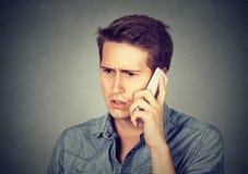 Homme réagissant sur l'entretien de téléphone photographie stock