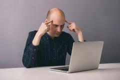 Homme réfléchi avec l'ordinateur portable Photo stock