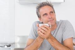 Homme réfléchi ayant le café dans la cuisine Image libre de droits