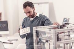 Homme réfléchi faisant le modèle sur l'imprimante 3D photo stock