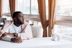 Homme réfléchi s'asseyant dans le café Image stock