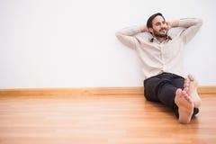 Homme réfléchi se penchant contre le mur avec les bras croisés Photographie stock