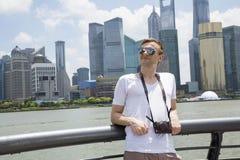 Homme réfléchi se penchant sur la balustrade contre la place financière du monde de Changhaï Photographie stock libre de droits
