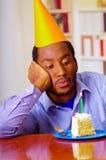 Homme réfléchi utilisant la chemise bleue et le chapeau se reposant par la table avec le morceau de gâteau dans l'avant, regardan Photographie stock libre de droits