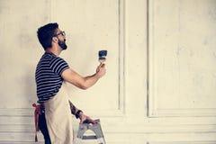 Homme rénovant le mur de maison photo stock