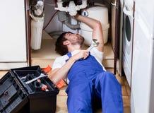 Homme réparant des tuyaux dans la cuisine Images libres de droits