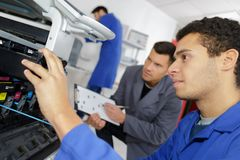 Homme réparant l'imprimante à l'école professionnelle photos stock