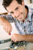 Homme réparant l'ordinateur avec le tournevis Images stock