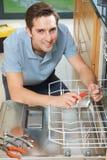 Homme réparant le lave-vaisselle domestique In Kitchen photo stock